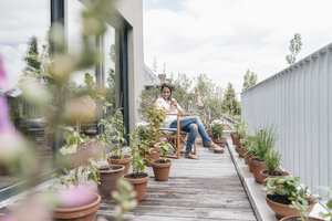 Smiling woman relaxing on balcony - JOSF01572
