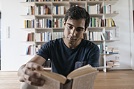 Young man reading book at home - JOSF01584
