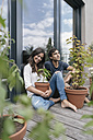 Happy couple with plants relaxing on balcony - JOSF01590