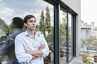Serious man on balcony looking away - JOSF01593