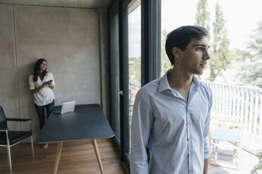 Young man looking out of window with woman in background - JOSF01596