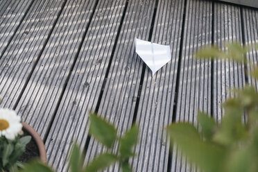 Paper plane on wooden terrace - JOSF01614