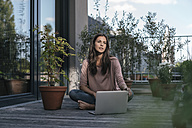 Woman with laptop sitting on balcony - JOSF01620