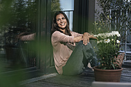 Smiling woman relaxing on balcony - JOSF01623