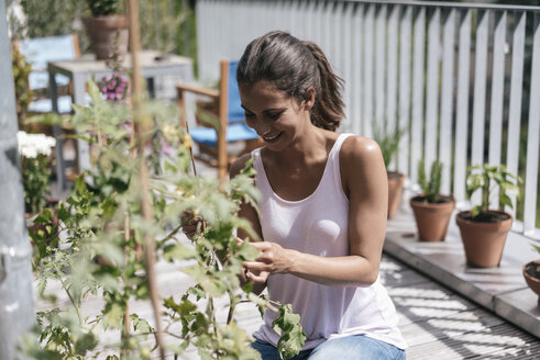 Smiling woman caring for plant on balcony - JOSF01626
