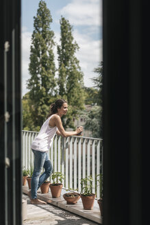 Smiling woman relaxing on balcony - JOSF01629