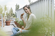 Smiling woman eating croissant with jam on balcony - JOSF01632