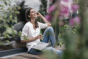 Happy woman with laptop and bottle sitting on balcony - JOSF01644