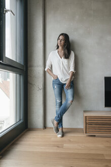 Woman standing at concrete wall - JOSF01650
