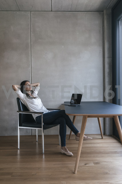 Woman sitting at table with laptop leaning back - JOSF01662 - Joseffson/Westend61