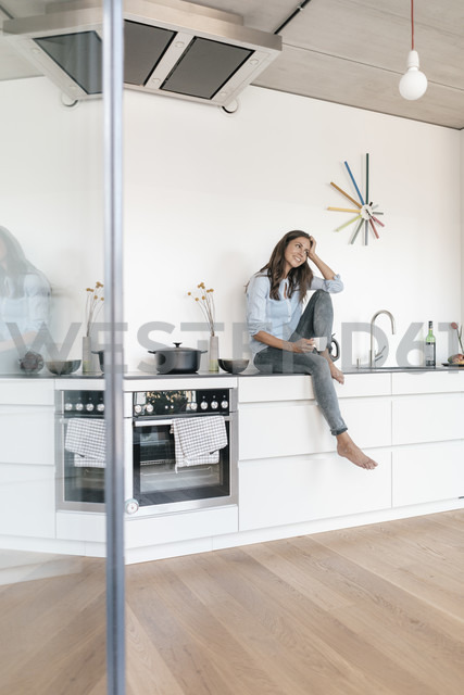 Smiling woman relaxing in kitchen at home - JOSF01671 - Joseffson/Westend61