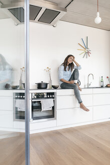 Smiling woman relaxing in kitchen at home - JOSF01671