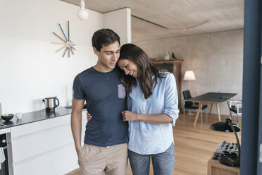 Happy couple hugging in kitchen at home - JOSF01674