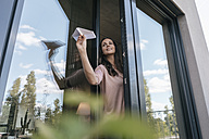 Woman holding paper plane at the window - JOSF01686