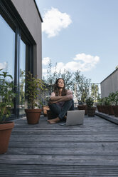 Woman with laptop sitting on balcony - JOSF01689