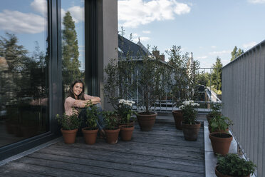 Smiling woman relaxing on balcony surrounded by plants - JOSF01692