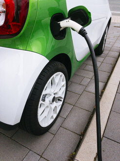 Germany, Lower-Saxony, Osnabrueck, Electric car being charged at a charging station. - HAWF00968