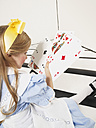 Little girl dressed up as Alice in Wonderland with oversized playing cards - FSF00954