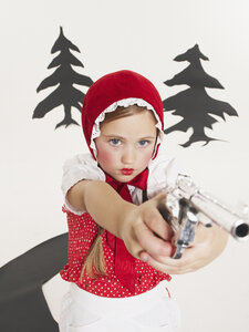 Little girl dressed up as Red Riding Hood holding pistol - FSF00966