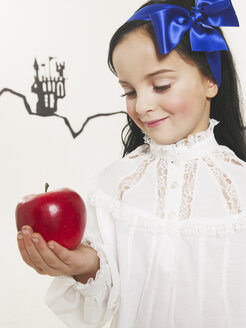 Portrait of little girl dressed up as Snow White looking at red apple - FSF00969