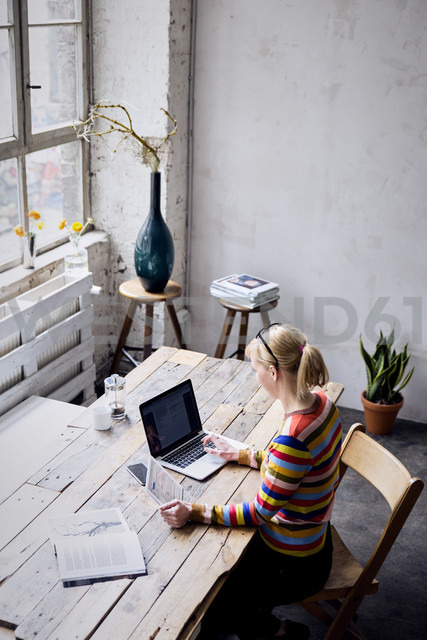 Woman sitting at desk in a loft using laptop and tablet - RBF05955