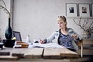 Woman working at desk in a loft - RBF05973