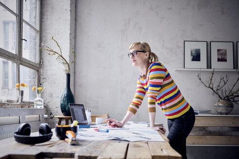 Portrait of smiling woman standing at desk in a loft looking through window - RBF05976
