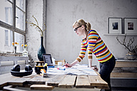 Woman working at desk in a loft - RBF05979