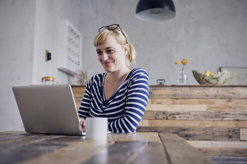 Portrait of smiling woman sitting at table using laptop - RBF06000