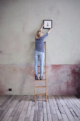 back view of woman on ladder hanging up picture frame in an unrenovated room of a loft - RBF06012