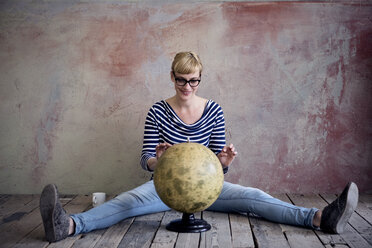 Smiling woman sitting on wooden floor in an unrenovated room looking at globe - RBF06015