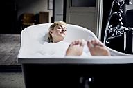 Blond woman taking bubble bath in a loft - RBF06018