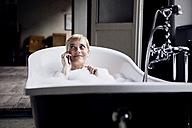 Portrait of smiling blond woman on the phone taking bubble bath in a loft - RBF06021