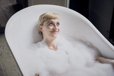 Portrait of happy woman taking bubble bath - RBF06024