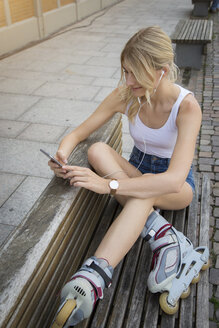 Smiling young inline-skater sitting on bench listening music with earphones and cell phone - JUNF00896