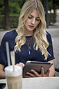 Portrait of blond woman sitting at sidewalk cafe looking at tablet - JUNF00902