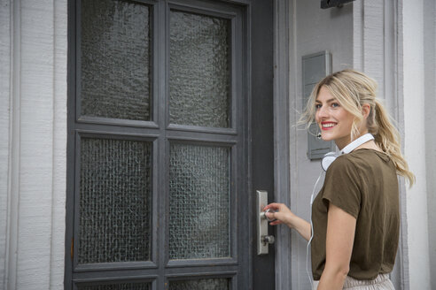 Portrait of smiling blond woman with headphones standing in front of entry door - JUNF00911