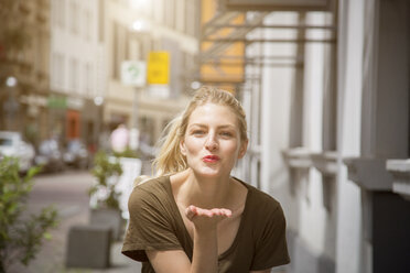 Portrait of happy blond woman blowing a kiss - JUNF00914