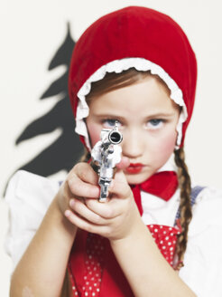 Little girl dressed up as Red Riding Hood holding pistol - FSF00974