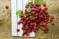 Raspberries, kitchen towel and leaves on wood - ASF06114