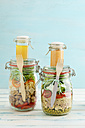 Preserving jars of mixed salads and jars of dressings - ECF01882