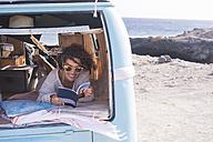 Spain, Tenerife, woman in parked van reading book - SIPF01707