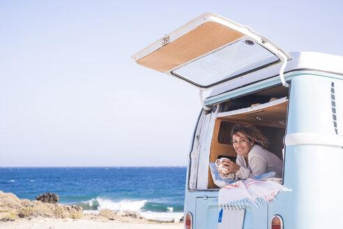 Spain, Tenerife, portrait of happy woman with coffee cup in van - SIPF01713