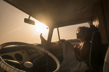 Spain, Tenerife, woman sitting in van at sunset - SIPF01737