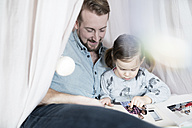 Father and daughter looking at photo album in toy teepee - SBOF00592