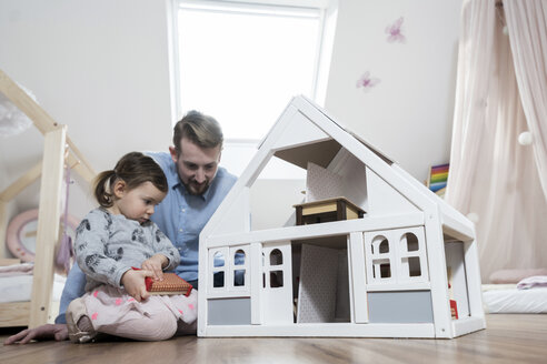 Father and toddler daughter playing with doll house in her nursery - SBOF00595