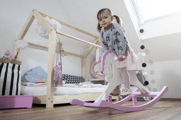 Toddler girl rocking on rocking horse in nursery - SBOF00598