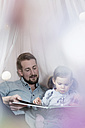 Father and daughter looking at photo album in toy teepee - SBOF00604