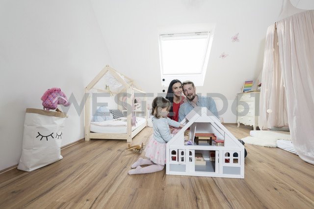 Happy parents in nursery while toddler daughter is playing with a doll house - SBOF00607 - Steve Brookland/Westend61