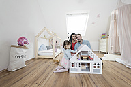 Happy parents in nursery while toddler daughter is playing with a doll house - SBOF00607